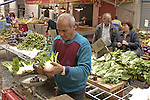 Vegetable vendor in market. Sicily, Italy