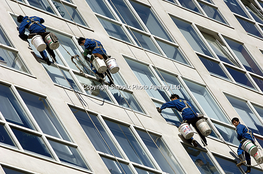 Chinese cleaners wipe the glass wall of Jianwai SOHO, Beijing, China..