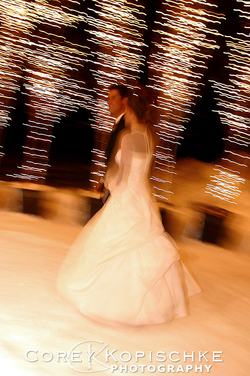 Bride and groom glide over the snow as the enter the church ceremony in Steamboat springs Colorado.