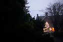 Christmas Decorations and lights at Nightime Street scene in Cotswold Village  CREDIT Geraint Lewis