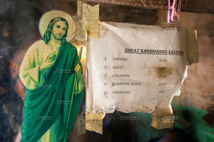 Nigeria. Enugu State. Enugu. Local hairdresser. Great barbrining saloon. A sticker with Jesus Christ and a list of prices taped on the mirror. Enugu is the capital of Enugu State, located in southeastern Nigeria. 28.06.19 © 2019 Didier Ruef