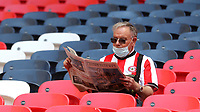 A Brentford fan relaxes by reading a newspaper ahead of kick-off during Brentford vs Swansea City, Sky Bet EFL Championship Play-Off Final Football at Wembley Stadium on 29th May 2021