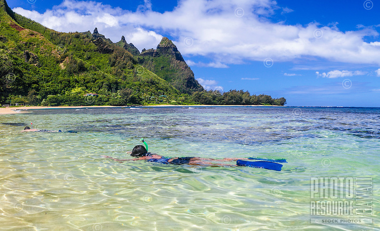 A couple snorkel in the shallows at Tunnels Beach on Kaua'i; Mt. Makana (or Bali Hai) is in the distance.