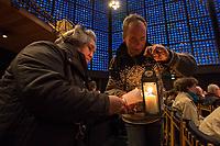 """Friedenslicht von Bethlehem kommt als Zeichen gegen Terror und Gewalt nach Berlin.<br /> Die Kaiser-Wilhelm-Gedaechtnis-Kirchengemeinde empfing am dritten Adventssonntag das Friedenslicht von Bethlehem. Mehr als 500 Pfadfinderinnen und Pfadfinder brachten das Licht in die Kirche, wo es mit einem oekumenischen Gottesdienst empfangen wurde. Die Gedaechtniskirche wurde von den Pfadfinderverbaenden als Ort fuer die Uebergabe des Lichtes ausgewaehlt, um kurz vor dem Jahrestag des Anschlags auf dem Breitscheidplatz ein Zeichen gegen Terror und Gewalt zu setzen. <br /> Das Licht wird bei den Gedenkandachten und -veranstaltungen am 19. Dezember 2017, dem Jahrestag des Anschlags, als Quelle aller Kerzenflammen, z.B. auch bei der Lichterkette am Abend dienen.<br /> Das Friedenslicht ist eine Initiative des Oesterreichischen Rundfunks (ORF). Es wird seit 1986 in der Geburtsgrotte Jesu in Bethlehem von einem Kind entzuendet und nach Wien gebracht. Als Symbol fuer den Wunsch nach Frieden und der Sehnsucht nach einer gerechten und solidarischen Welt tragen Pfadfinderinnen und Pfadfinder das Licht am dritten Advent in ihre Heimatlaender. In Deutschland steht die diesjaehrige Friedenslichtaktion unter dem Motto: """"Auf dem Weg zum Frieden"""".<br /> In der Kaiser-Wilhelm-Gedaechtnis-Kirche wird das Friedenslicht bis zum Ende der Weihnachtszeit in einer Leuchte an einem zentralen Ort brennen. An der Flamme kann jeder eine Kerze entzuenden und das Licht auf diese Weise an andere Menschen weitergeben – beispielsweise in Kirchengemeinden oder Schulen.<br /> Im Bild: Gottesdienstteilnehmer geben geben das Licht untereinander weiter.<br /> 17.12.2017, Berlin<br /> Copyright: Christian-Ditsch.de<br /> [Inhaltsveraendernde Manipulation des Fotos nur nach ausdruecklicher Genehmigung des Fotografen. Vereinbarungen ueber Abtretung von Persoenlichkeitsrechten/Model Release der abgebildeten Person/Personen liegen nicht vor. NO MODEL RELEASE! Nur fuer Redaktionelle Zwecke. Don't publish without copyr"""