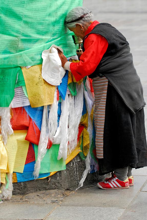 Tibetan woman with prayer wheel, praying at prayer-flag pole, or darchen, on the Barkhor pilgrim circuit, outside the Jokhang Temple, Lhasa, Tibet.