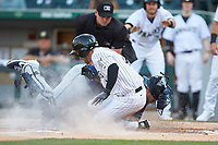 Charlie Tilson (4) of the Charlotte Knights is tagged out at home plate by Toledo Mud Hens catcher Cameron Rupp (26) as home plate umpire Jeremy Riggs looks on at BB&T BallPark on April 24, 2019 in Charlotte, North Carolina. The Knights defeated the Mud Hens 9-6. (Brian Westerholt/Four Seam Images)