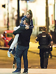 © Joel Goodman - 07973 332324 . 23/05/2017. Manchester, UK. A man lifts a girl , believed to be his daughter , as she leaves the arena . Anxious parents wait by the police cordon for news of children inside the Manchester Arena . Police and other emergency services are seen near the Manchester Arena after reports of an explosion. Police have confirmed they are responding to an incident during an Ariana Grande concert at the venue. Photo credit : Joel Goodman