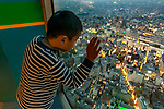 Child peers out the window of a skyscraper in Tokyo, Japan.