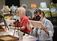 Leslie Belden (right) of Fayetteville begins a painting Friday, Oct. 8, 2021, during the Oil Painting for Beginners - Landscape class offered by the University of Arkansas Osher Lifelong Learning Institute at the Fayetteville Executive Airport in Fayetteville. The two-hour class is taught over the course of two sessions with participants learning hands-on how to paint a landscape scene. Visit nwaonline.com/211009Daily/ for today's photo gallery.<br /> (NWA Democrat-Gazette/Andy Shupe)