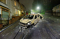 """Pictured: Two of the burned out cars outside the house of Adam Romain in Waun-Wen Road in the Mayhill area of Swansea, Wales, UK. Thursday 20 May 2021<br /> Re: Gangs of """"yobs"""" have been setting fire to cars and rolling them down a hill in Swansea, Wales, UK.<br /> South Wales Police said they attended """"large scale disorder"""" in the Mayhill area of the city on Thursday evening."""