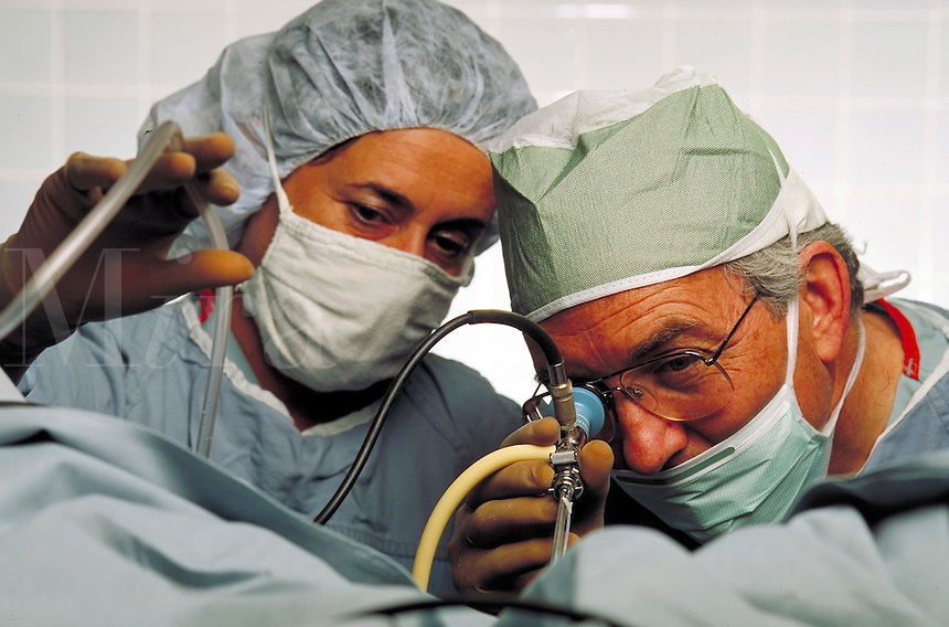 Obstetrician gynecologist surgeon conducts endoscopic surgery.