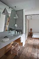 An ensuite bathroom clad in white marble adjoins the simple monastic bedroom