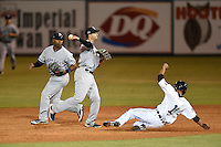 Tampa Yankees shortstop Tyler Wade (17) turns a double play as second baseman Angelo Gumbs (21) backs up the play with Ismael Salgado (1) sliding in during a game against the Lakeland Flying Tigers on April 9, 2015 at Joker Marchant Stadium in Lakeland, Florida.  Tampa defeated Lakeland 2-0.  (Mike Janes/Four Seam Images)