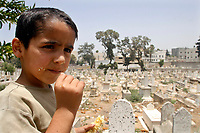 """Gaza.June.22.2008.Mohammed Jilo  a six-year-old  Playing among graves, he was born and grew up in the cemetery , """"he don't go out from this place and he don't fear from the tombs because we live and play here.""""The family was drove out from their original village in the 1948 when Jews forced thousands of Palestinians to migrate, establishing the State of Israe.June.22.2008l.""""photo by Fady Adwan/propaimages"""""""