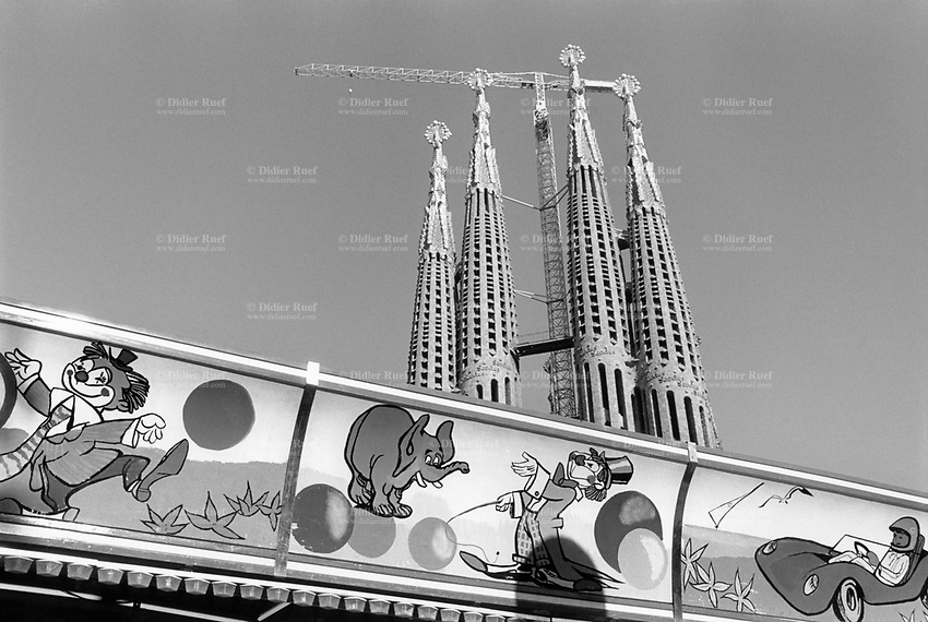 Spain. Autonomous community of Catalonia. Barcelona. The Basilica de la Sagrada Familia, also known as the Sagrada Familia, is a large unfinished Roman Catholic minor basilica. Designed by the Spanish architect Antoni Gaudí (1852–1926), his work on the building is part of a UNESCO World Heritage Site. Amusement park with funny drawings (a clown with ball, elephant and animal trainer, sport car and driver). Barcelona is the capital and largest city of the autonomous community of Catalonia. © 1987 Didier Ruef