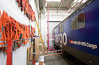 Switzerland. Canton Ticino. Bellinzona. Officine FFS. Stabilimento Industriale SBB CFF FFS Cargo. Railway workers on strike. Building's occupation. Locomotive. The orange clothes of the blue collar workers are hanged on the wall. © 2008 Didier Ruef