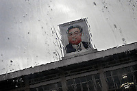 """A picture of the late leader of North Korea, Kim Il-Sung, is seen through a rain covered window in Pyongyang, North Korea (DPRK) on 25 August, 2007. After his death, he was designated in the constitution as the country's """"Eternal President"""" though North Koreans generally refer to him as the """"Great Leader."""""""