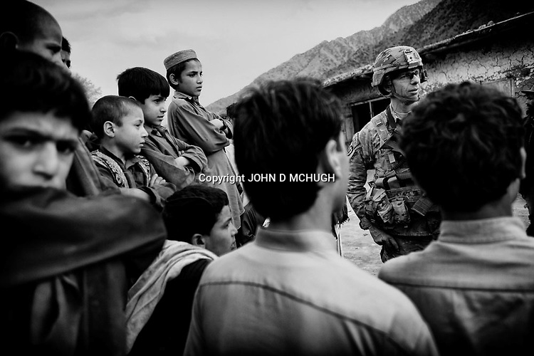"""US Army Lieutenent Colonel Dan Wilson, Battalion Commander of 2/27 Infantry, 25th Infantry Division, chats with local Afghan boys in Nishigam village, Kunar Province, 05 December 2011. LTC Wilson asked the boys if there was anything he could get to make their lives better, to which they replied in unision, """"Cricket bats."""" (John D McHugh)"""