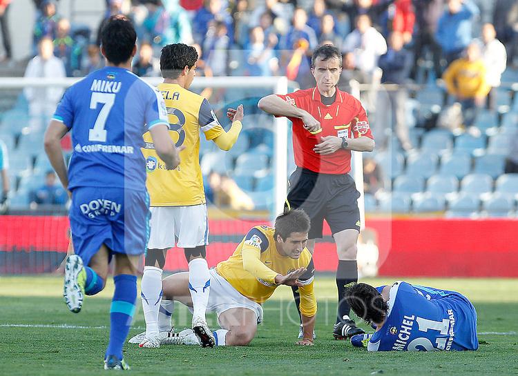 Getafe's Michel injured (r) and Real Sociedad's Markel Bergara (l) in presence of the referee Fernandez Borbalan (c) during La Liga match.March 17,2012. (ALTERPHOTOS/Acero)