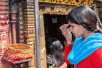 Nepal, Kathmandu.  Hindu Woman Applying a Bindi of Kumkuma Powder to her Forehead before Entering the Ashok Binayak (Maru Ganesh) Temple, Durbar Square.