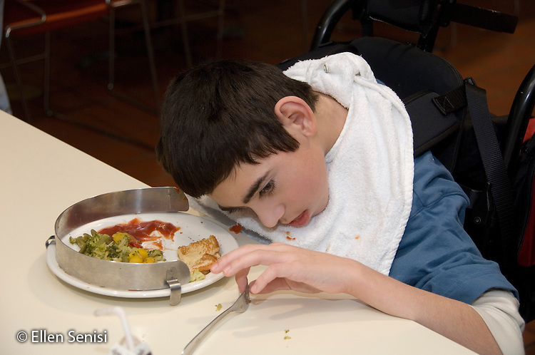 MR / Albany, NY.Langan School at Center for Disability Services .Ungraded private school which serves individuals with multiple disabilities.Child grasps utensil to feed himself.  Plate has a guard to keep food from being pushed off. Student wears clothing protector to help stay clean while dining. Boy: 11, cerebral palsy, expressive and receptive language delays.MR: Bro12.© Ellen B. Senisi