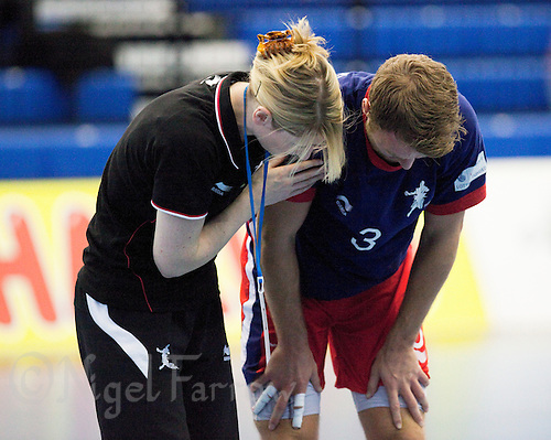 08 JAN 2012 - LONDON, GBR - Great Britain's physiotherapist Diane Slater (left, in black) helps Great Britain playmaker Ciaran Williams (right, in blue and red) after he injured himself during the teams warmup before the men's 2013 World Handball Championships qualification match against Austria at the National Sports Centre in Crystal Palace, Great Britain (PHOTO (C) 2012 NIGEL FARROW)