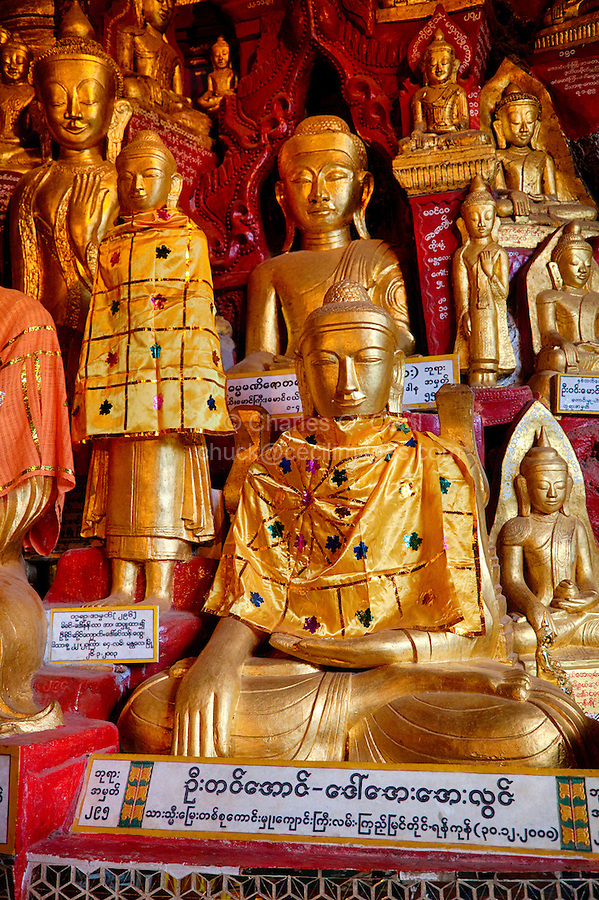 """Buddha Statues in Shwe Oo Min Cave, Pindaya, Shan State, Myanmar, Burma.  The Buddha in front demonstrates the bhumisparsha mudra (gesture), """"calling the earth to witness,"""" with the right arm hanging down over the right knee, palm inward, fingers down, touching the earth.  The left hand rests in the lap, palm upward."""