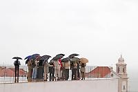 A group of tourists huddling under umbrellas in rain at the Miradouro de Santa Luzia. Street view. Alfama district. Lisbon, Portugal