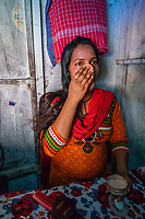 India; Maharashtra; Mumbai; Bombay. The red light district, Kamatipura. In her room where she works as a sex-worker in the brothel. Nasima Shaikh (Rani) is from Kolkata. She was married at the age of 16 to a man from the same city. He told her that he would take her to Mumbai but instead, took her to Nasik where they stayed at his aunt's house. After 3 days he told Nasima that he had to leave because of an urgent work. He went to his hometown leaving Nasima with his uncle and aunt, but she was unaware of the evil intentions they had in their mind about her. They brought her to RLA in K.P 12th lane and sold her there to a brothel. They told her to stay there for a while and that they will come back soon to take her. Nasima patiently waited a whole day expecting them to come back but that didn't happen. Next day her madam (brothel-keeper) woke her up early and told her to take a bath and be ready. She also made her cut her hair short. She was forced to do make-up and stand on the street. At first Nasima use to cover her body with a scarf, but her landlady didn't like that and told her to remove it.<br />       Whenever she refused to do this work she was beaten severely by her many times. Her madam told her that your uncle and aunt have sold you here and now it's your responsibility to pay me by working here. In the beginning she didn't like men coming and touching her but later she compromised. She agreed to sleep with them, against her will as the landlady forced her and she had to support her two children who were living in the village with her parents. She was completely devastated, feeling alone and hopeless. <br />        She has been in this business for 15 years. One day our Savera staff met Nasima and made a good relationship with her by frequently visiting her during outreach. After few days, we told her about our tailoring course and she happily accepted our call. She says that after joining Savera she founded joy, peace and life of freedom.   She makes about $