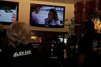 """Friday, October 3, 2008 Ocean Beach CA USA:  Locals in the Arizona bar and resturant on Bacon street discuss the new TV show """"Ex List"""" premiere as it plays on multiple screens in the background."""
