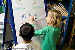 """Education Elementary school Grade 1 mathematics dry erase board with """"greater than"""" """"less than"""" activity two students working one boy and one girl vertical"""
