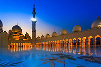 Sheikh Zayed Grand Mosque columns lit up and reflecting at twilight on the amazing floral mosaic of semi-precious stones and marble in Abu Dhabi Asia