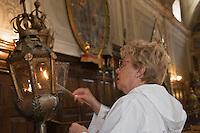 Europe/France/Provence-Alpes-Côtes d'Azur/06/Alpes-Maritimes/Alpes-Maritimes/Arrière Pays Niçois/Sospel: Jeanine Bensa  et son époux Donnat en tenue de pénitent allument les fanaux  de procession dans la Chapelle des Pénitents Blancs