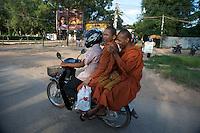 Siem Reap street scene, three Monks on the back of a Motor Bike, Cambodia