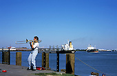 New Orleans, USA. Woman plays trombone by Mississippi River with large cargo ships behind and red tin for money on ground.
