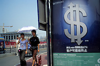 Two Chinese girls walk by a sign of US dollar on a billboard in Beijing, China..