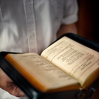 A man reads a leather-bound Legionaries of Christ prayer book. The Legion of Christ is a conservative Roman Catholic congregation whose members take vows of chastity, obedience and poverty.