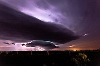Purple supercell severe thunderstorm illuminated by lightning at night in New Mexico, June 12, 2012