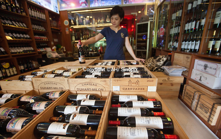 A wine trader holds a 1.5 litre bottle of Moulin de Duhart Paulliac 2009 which sells for RMB7,330.00 at the official Chinese government-owned Guangzhou Friendship Store across town. But she was selling it for just RMB1,230.00 – about a hundred pounds.<br /> <br /> PHOTO BY SINOPIX