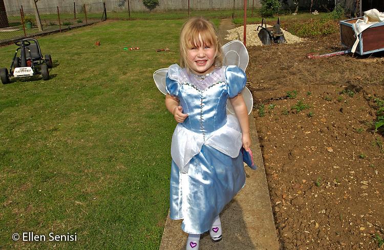MR / Radley, Abingdon, Oxfordshire, England.Girl (5) in dress-up clothes plays in her backyard..MR: Web4.©Ellen B. Senisi