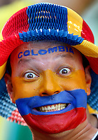 A Colombia fan with painted face cheers his side on