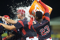 Batavia Muckdogs Javier Lopez (23) dumps the water bucket onto teammates, including Mike King (22) after a walk off win against the Mahoning Valley Scrappers on August 18, 2016 at Dwyer Stadium in Batavia, New York.  Batavia defeated Mahoning Valley 2-1 in twelve innings. (Mike Janes/Four Seam Images)