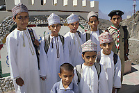 Wadi Bani Kharus, Oman, Arabian Peninsula, Middle East - Omani Schoolboys, one in his Boy Scout Uniform.  Most wear the traditional embroidered Omani cap, the kummah.   A white or tan tassel several inches long, called a kashkusha or a frakha, hangs from the right side of the neckline of each dishdasha (white robe).  The kashkusha is often perfumed.