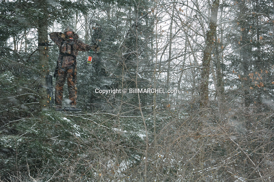 00105-043.20 Bowhunting (DIGITAL) Archer is in tree stand in balsam fir during snow storm.  Hunt, cold, late season, deer, winter.  H3R1