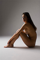 Nude woman sitting, side view