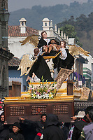 Antigua, Guatemala.  Good Friday Procession.  Señor Sepultado, Christ after the Crucifixion, being carried on an anda (float) by Cucuruchos in Black.