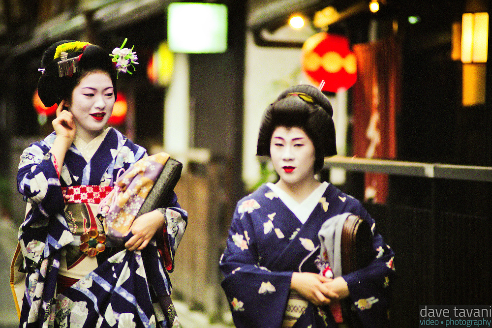 Two geishas stroll down a street in Kyoto Japan's famous Gion Corner geisha district.