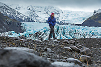 Woman walking in front of glacier and mountains in the background, Iceland