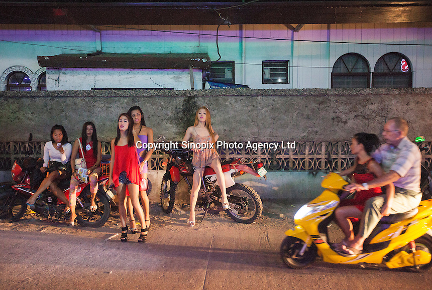 A man and a young Filipina on a motercycle pass transgender prostitutes and female prostitutes in Angeles City, Republic of the Philippines, 08 November 2014. The 'sin city', which sprung up on the fringes of a US Air Force base during the Vietnam war, has a reputation for cheap sex, and was a favourite destination for alleged murderer Rurik Jutting, who used to fly to Angeles City from Hong Kong for debauched weekends. The British banker is currently on remand at a secure facility in Hong Kong for allegedly murdering two Indonesian prostitutes in his flat whilst high on alcohol and cocaine.