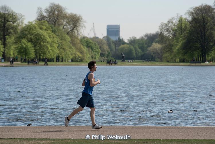 Young man jogging, Kensington Gardens, London.